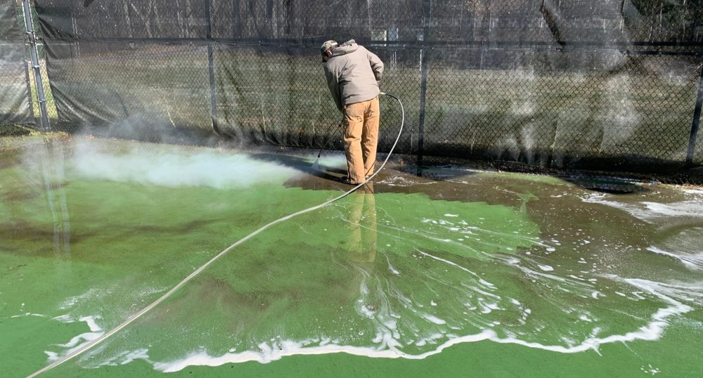 Pressure washing the tennis courts